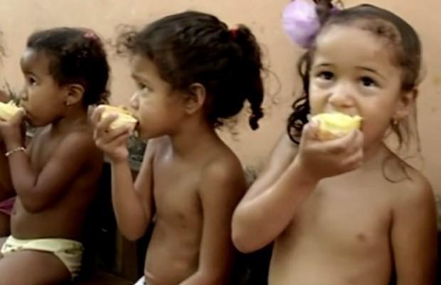 Crianças comem laranja durante o lanche em creche de Porangatu, Goiás (Foto: Reprodução/ TV Anhanguera)