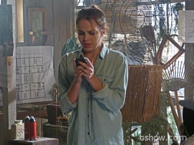 Anita com celular de Antônio na cabana (Foto: Malhação / Tv Globo)