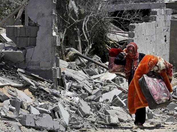 Mulher retira pertences de orpedui destrupido em Beit Lahiya, no norte da Faixa de Gaza (Foto: Adel Hana/AP)