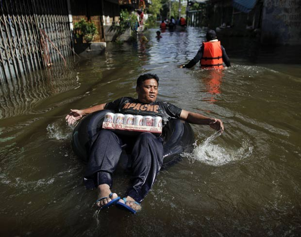 Em outubro de 2011, um homem foi flagrado remando um bote feito com uma câmara de pneu em uma área alagada em Bangcoc, na Tailândia, enquanto carregava uma caixa de cerveja (Foto: Damir Sagolj/Reuters)