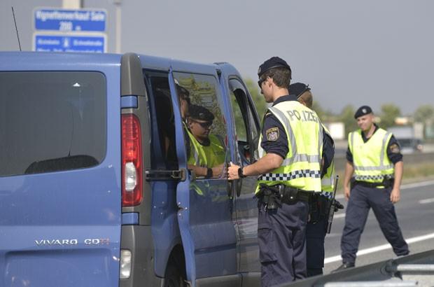 Policiais austríacos inspecionam veículo perto da fronteira com a Hungria em busca de imigrantes ilegais nesta segunda-feira (31) (Foto: Hans Punz/AP)