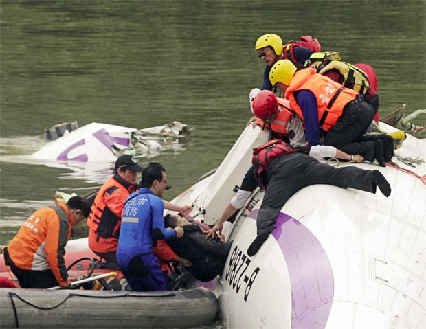Passageiro é retirado do avião caído na água (Foto: Pichi Chuang/Reuters)
