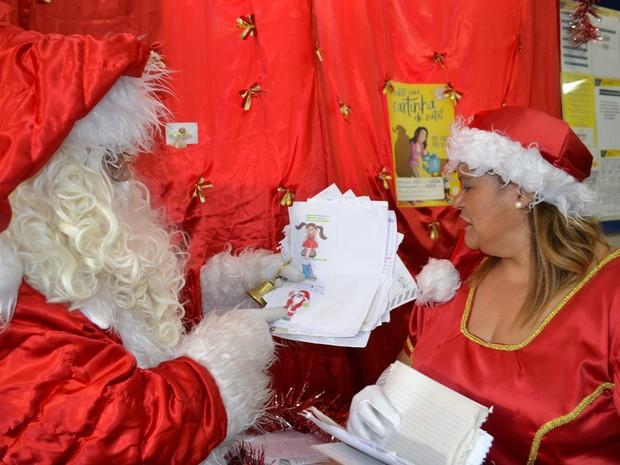 Com ajuda da Mamãe Noela, Papai Noel lê atentamente as cartinhas que já recebeu em Mogi das Cruzes (Foto: Maiara Barbosa/ G1)
