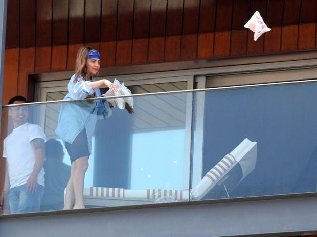 Da sacada do hotel onde está hospedada, Lady Gaga joga saco de biscoitos de polvilho para fãs no Rio de Janeiro (Foto: Delson Silva/AgNews)