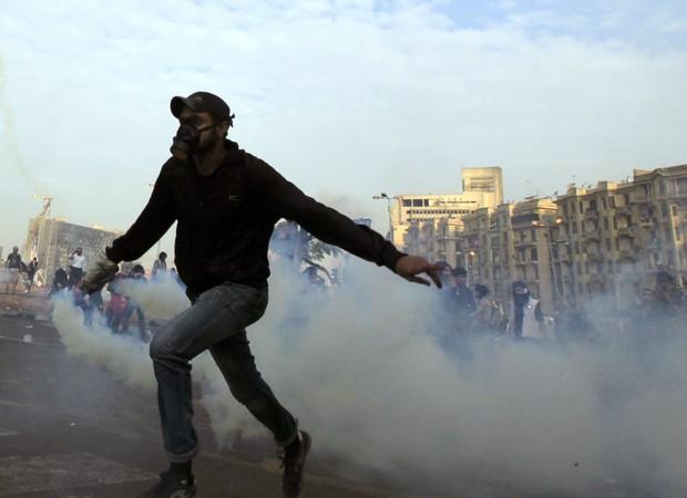Manifestante joga de volta bomba de gás lacrimogêneo lançada por forças de segurança próximo à praça Tahrir, no Cairo, capital do Egito (Foto: Mohamed Abd El Ghany/Reuters)