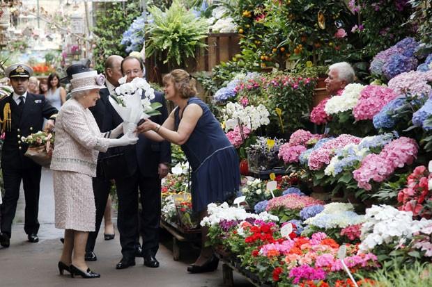 A rainha da Inglaterra, Elizabeth II, ganha flores em mercado de Paris que ganhará seu nome (Foto: Francois Mori/AFP)