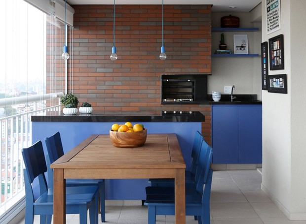 O mesmo tom de azul da cozinha norteou o décor do espaço. Pendentes da Decorlight. Cadeiras da Oppa. Mesa de madeira e armário revestido em laca azul projetados pela GF Projetos  (Foto: Mariana Orsi/Divulgação)