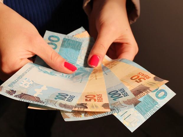Cédulas de real nas mãos de uma pessoa. notas, dinheiro, reais, dólares, cotação, câmbio, valor, economia. -HN- (Foto: Marcos Santos/USP Imagens)