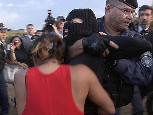 Policial arrasta manifestante com máscara em frente ao Congresso Nacional nesta quinta-feira (5) (Foto: TV Globo/Reprodução)