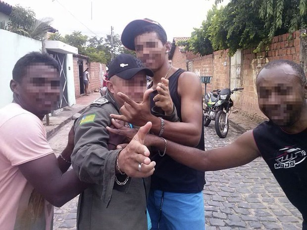 Fotografia mostra o mesmo homem fardado já simulando ter sido imobilizado (Foto: Reprodução/Facebook)