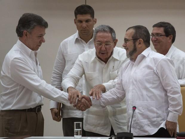 O presidente colombiano Juan Manuel Santos e o líder das Farc Timoleón Jiménez apertam as mãos na frente do presidente cubano raúl Castro, após anunciarem acordo de transição à paz na Colômbia (Foto: AP Photo/Desmond Boylan)