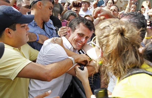 O candidato oposicionista à presidência da Venezuela, Henrique Capriles, é saudado ao votar neste domingo (7) (Foto: AFP)