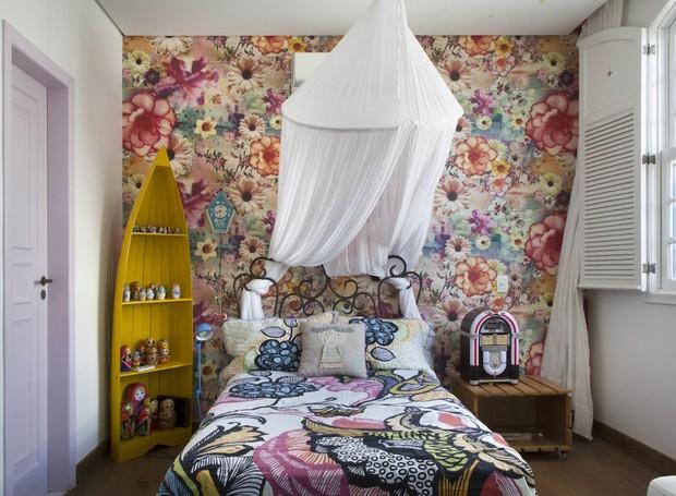 O quarto da Manu tem uma parede forrada com tecido de padronagem floral, da JRJ Tecidos, em total harmonia com o mosquiteiro sobre a cama e a estante-canoa amarela. O projeto de Camila Urbanetto (Foto: André Nazareth)