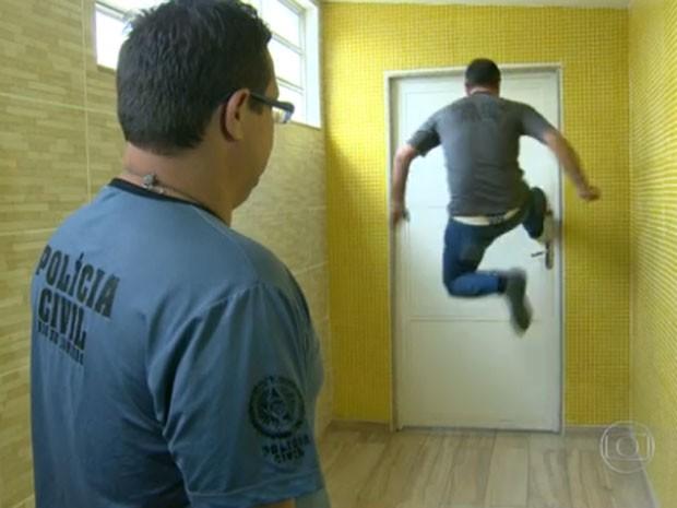 Policiais tentam arrombar porta durante operação (Foto: Reprodução / Globo)