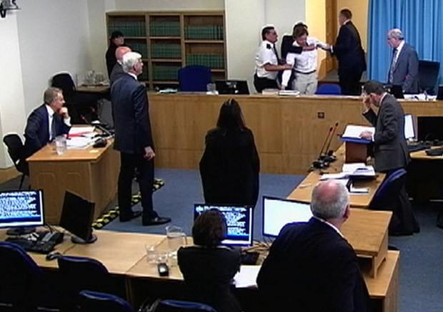 Imagem de TV mostra o manifestante sendo retirado por seguranças durante depoimento de Tony Blair (sentado à esquerda) (Foto: Reuters)