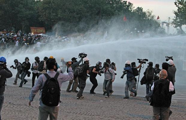 Manifestantes e jornalistas fogem dos canhões de água da polícia durante uma operação para evacuar o Parque Gezi em Istambul (Foto: Thanassis Stavrakis/AP)
