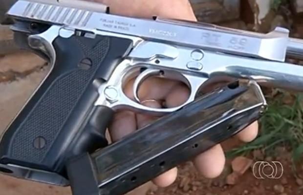 Policial mostra arma usada no crime, em Anápolis, Goiás (Foto: Reprodução/ TV Anhanguera)