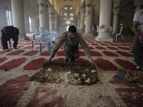 Palestinos limpam a mesquita Al-Aqsa após confronto com policiais israelenses  (Foto: Reuters/Ammar Awad)