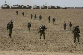 Soldados israelenses caminham em campo próximo à Faixa de Gaza, na Palestina. (Foto: Baz Ratner/Reuters)