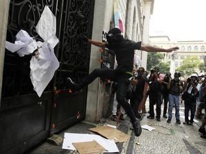 Manifestante chuta uma das portas da Câmara (Foto: Pilar Olivares/Reuters)