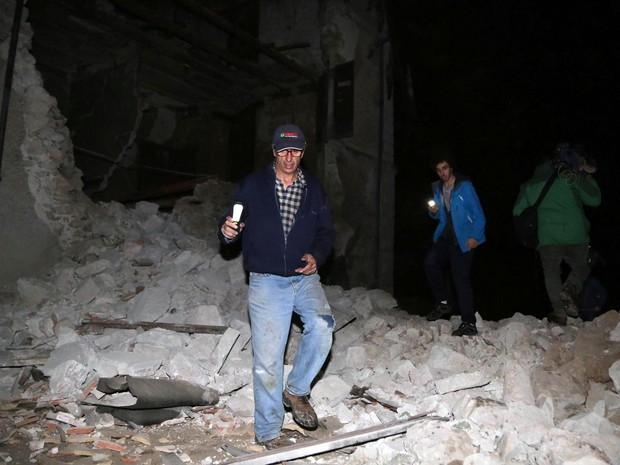 Moradores caminham entre escombros na vila de Visso, na Itália, após terremoto atingir o local na quarta (26 (Foto: Matteo Crocchioni/ANSA via AP)