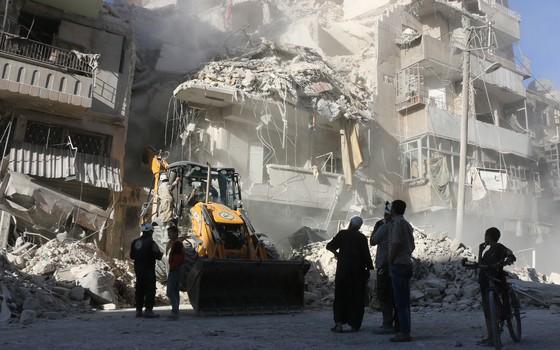 Um trator limpa o entulho que restou após ataques aéreos em Alepo, na Síria (Foto: THAER MOHAMMED / AFP)