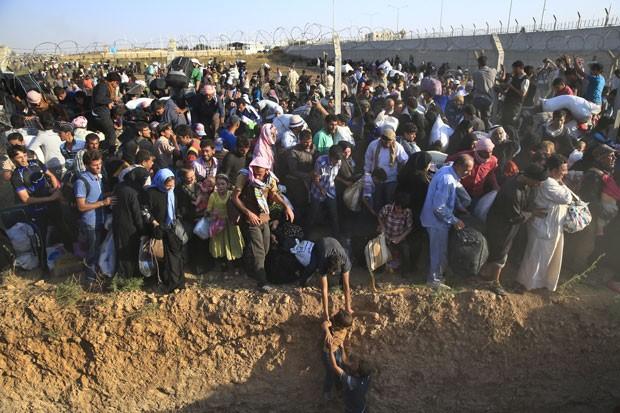 A Turquia começou a deixar entrar em seu território neste domingo (14) os sírios que estão fugindo dos combates entre curdos com os jihadistas do grupo Estado Islâmico (EI) na cidade fronteiriça de Tall Abyad (Foto: Lefteris Pitarakis/AP)