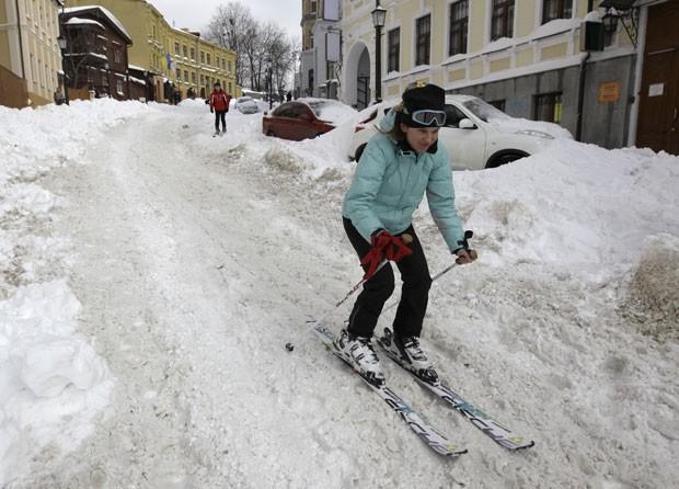 Mulher foi flagrada esquiando em rua coberta de neve na Ucrânia (Foto: Sergei Chuzavkov/AP)