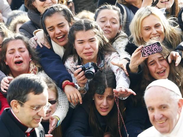 Jovens fiéis tietam o Papa Francisco tentando tirar fotos e falar com o Pontífice na chegada dele à Praça de São Pedro, no Vaticano, onde realiza audiência semanal (Foto: Tony Gentile/Reuters)