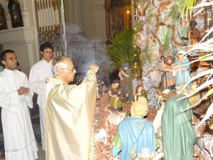 Pároco iniciou a missa colocando a imagem do menino Jesus no Presépio (Foto: Michelle Farias/G1)