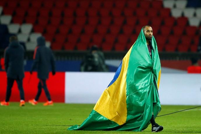 Lucas se enrola em bandeira do Brasil após jogo PSG x Angers em homenagem à Chapecoense (Foto: Gonzalo Fuentes/Reuters)