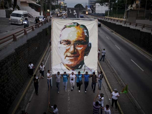 Manifestantes carregam cartaz com foto de Oscar Arnulfo Romero durante marcha pelo aniversário de 35 anos de sua morte neste sábado (21) em San Salvador (Foto: REUTERS/Jose Cabezas)
