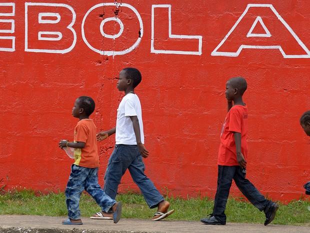 Crianças caminham junto a anúncio de campanha contro o ebola em Monrovia, na Libéria (Foto: Dominique Faget/AFP)