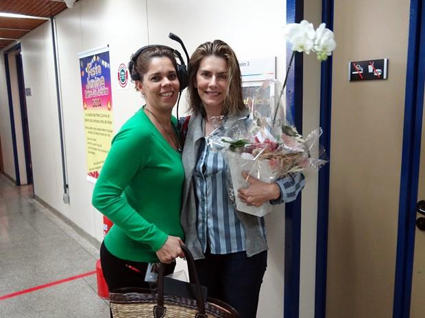 Em nome de toda a equipe da novela, a coordenadora de produção Daniela entrega as flores a Maitê (Foto: Gabriela / TV Globo)