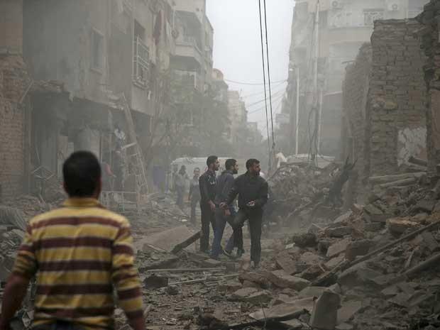 Moradores inspecionam danos em região bombardeada em Damasco oriental. Ataques atingiram um hospital (Foto: Bassam Khabieh / Reuters)