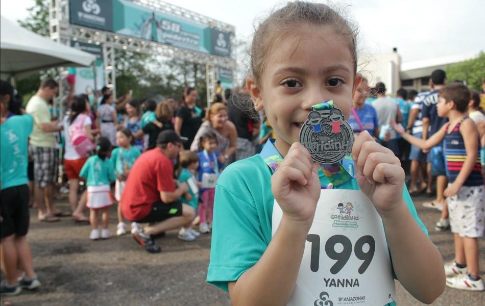 Orgulhosa, a pequena Yanna exibe a sua medalha  (Foto: Katiúscia Monteiro/Rede Amazônica)