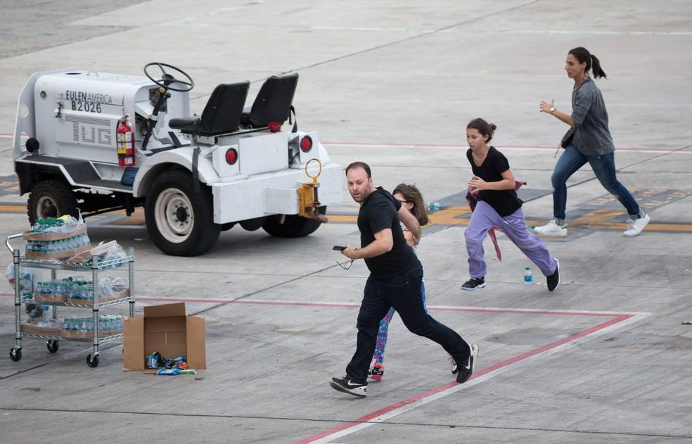 Pessoas correm na pista do Aeroporto Internacional de Fort Lauderdale-Hollywood, na Flórida, nos EUA, após um atirador abrir fogo dentro do terminal 2. Cinco pessoas morreram e oito ficaram feridas no ataque (Foto: Wilfredo Lee/AP)