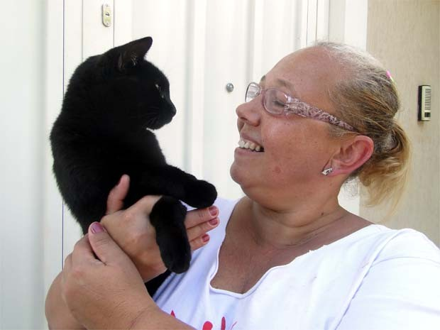 A gata Teca é só carinho com Valéria, que a salvou de ser jogada no rio (Foto: Eduardo Guidini/ G1)