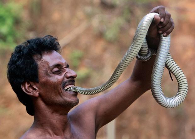 Em seus shows, Sajal Biswas chega a colocar a cabeça da cobra na sua boca (Foto: Jayanta Dey/Reuters)