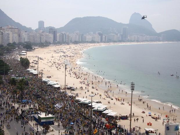 Num dia nublado, as areias de Copacabana praticamente vazias contrastam com as pistas tomadas por manifestantes (Foto: Rodrigo Gorosito/ G1)