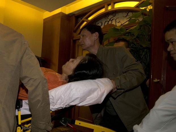 Mulher sai carregada após receber a notícia sobre o avião da Malaysia Airlines (Foto: Ng Han Guan/AP)