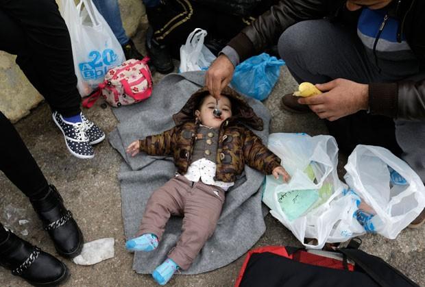 Síria alimenta seu bebê em área onde estão refugiados e imigrantes no porto de Piraeus, em Atenas (Foto: Thanassis Stavrakis/AP)