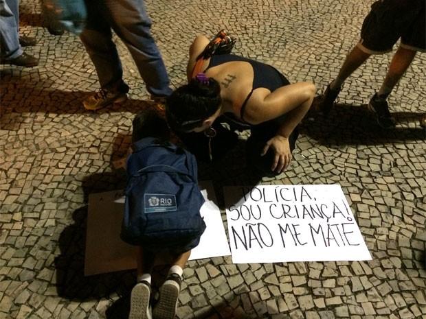 Criança e mulher usam cartazes para protestar (Foto: Marcelo Elizardo/G1)