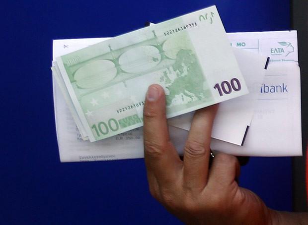 Grego mostra euros sacados nesta quarta-feira (13) em caixa eletrônico na região central de Atenas (Foto: AFP)