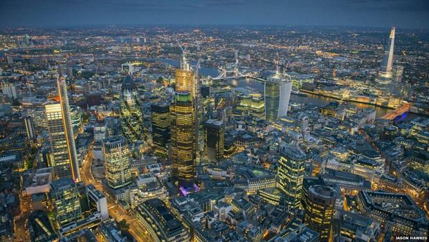 O fotógrafo Jason Hawkes, que sobrevoa Londres regularmente em um helicóptero AS355, divulgou uma série de fotos da cidade, incluindo esta imagem aérea noturna dos novos arranha-céus da capital britânica.  (Foto: Jason Hawkes)