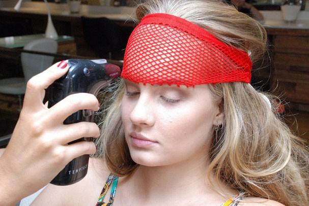 Terceiro passo: com meia arrastão amarrada na testa, use airbrush pra aplicar purpurina branca, garantindo o efeito escama (Foto: Manu Tabosa)