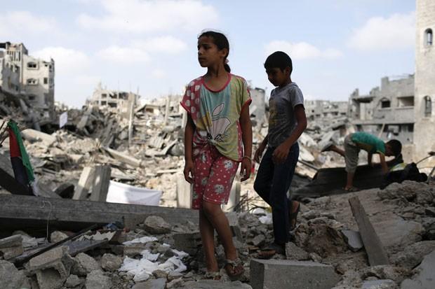 Crianças são vistas em meio a ruínas de prédios na cidade de Gaza nesta terça-feira (12) (Foto: Siegfried Modola/Reuters)