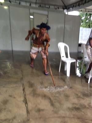 Índio usa rodo para escoar água da chuva que caiu em alojamento (Foto: João Bandeira de Mello/ G1)