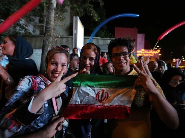 Iranianos seguram a bandeira e fazem o sinal da vitória ao comemorar o acordo sobre o programa nuclear do Irã nesta terça em Teerã (Foto: AFP PHOTO/ATTA KENARE)
