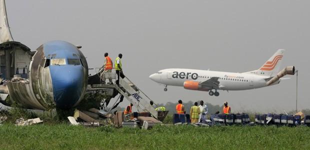 Avião aterrissa no aeroporto de Lagos enquanto uma aeronave abandonada é desmontada.  (Foto: Sunday Alamba/AP)